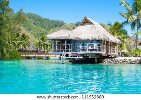 Luxury over water bungalow in green lagoon. Tahiti - stock photo