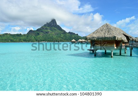Luxury overwater bungalow with a thatched roof in a honeymoon vacation resort in the clear blue lagoon with a view on Mt. Otemanu on the tropical island of Bora Bora, near Tahiti, in French Polynesia.