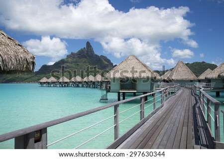 Luxury overwater bungalows with a thatched roofs in a honeymoon vacation resort in the clear blue lagoon with a view on Mt. Otemanu on the tropical island of Bora Bora, near Tahiti, French Polynesia. - stock photo