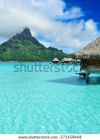 Luxury overwater honeymoon bungalows in a vacation resort in the clear blue lagoon with a view on Mt. Otemanu on the tropical island of Bora Bora, near Tahiti, in French Polynesia. - stock photo