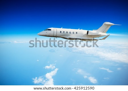 Luxury private jet plane flying above clouds in day light - stock photo
