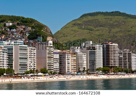 Luxury residential apartment and hotel buildings in the front of the Copacabana beach with mountains behind in Rio de Janeiro, Brazil - stock photo