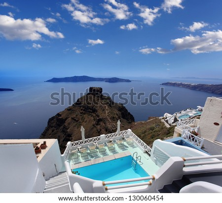 Luxury resort swimming pool in Santorini, Greece - stock photo