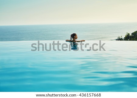 Luxury Resort. Woman Relaxing In Infinity Swimming Pool Water. Beautiful Happy Healthy Female Model Enjoying Summer Travel Vacation, Looking At Sea View. Summertime Recreation, Relax And Spa Concept. - stock photo