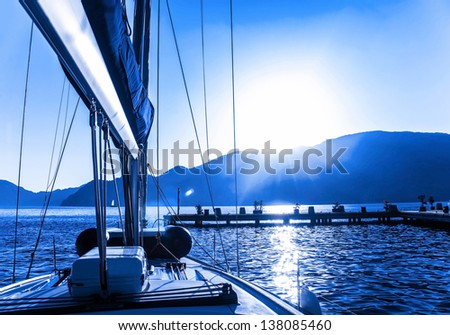 Luxury sail boat on the sea, sun down, beautiful seascape, summer vacation, yachting sport, traveling on water transport - stock photo