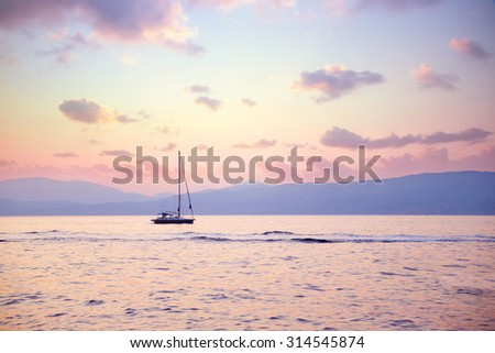 Luxury sailboat in beautiful pink sunset light on the sea, amazing view, luxury water transport, summer vacation concept - stock photo