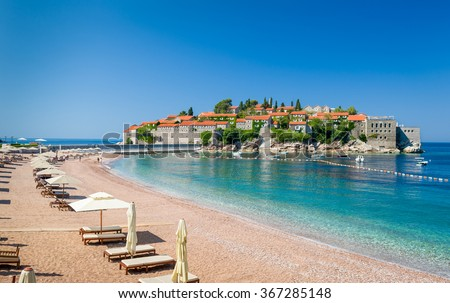 Luxury sand beach with wooden chaise-longue chairs and umbrellas near the Sveti Stefan historical town on the island. Montenegro.