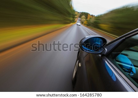 Luxury sedan driving fast in country road.