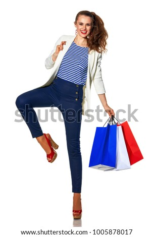 Luxury Shopping. The French way. Full length portrait of cheerful stylish woman in white jacket isolated on white background with shopping bags painted in the color of the French flag