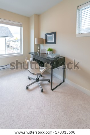 Luxury spacious modern nicely decorated den, home office with the table and the office chair. Interior design. Vertical.