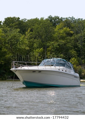 Luxury speed boat anchored next to shore. - stock photo