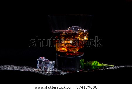 Luxury still life of whisky glass with ice and green leaf - stock photo