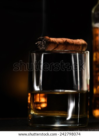 Luxury still life with cognac and cigar on a dark background. Close up shot with copyspace - stock photo
