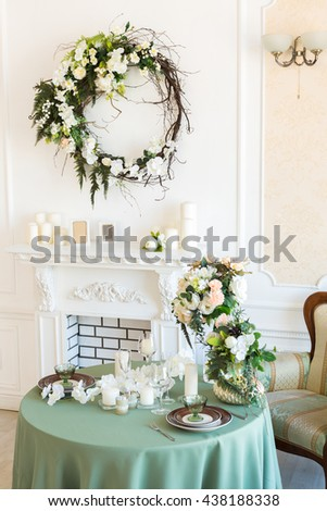 Luxury stylish bright light interior of sitting room. White walls dacorated by ornament. Firaplace. Nobody inside room. Table setting by dishes, candles and flower bouquets.