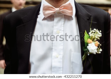 luxury stylish groom with boutonniere on elegant suit and bow tie close-up at wedding ceremony - stock photo