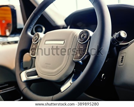 Luxury SUV Interior: Multifunctional steering wheel with control buttons and dashboard, shallow depth of field - stock photo