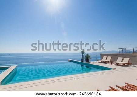 Luxury swimming pool and blue water at the resort with beautiful sea view - stock photo