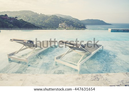 Luxury swimming pool and blue water at the resort with beautiful sea view  (Vintage filter effect used) - stock photo