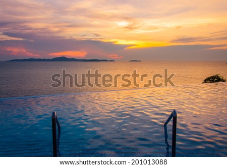 Luxury swimming pool in front of sea at during sunset - stock photo