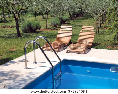 Luxury swimming pool with green grass and chairs