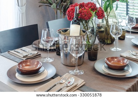 luxury table set on wooden dinning table with bottle of wine