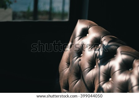 Luxury texture of leather furniture on Dark Background with light and shadow near the window - stock photo