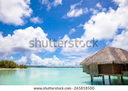 Luxury thatched roof honeymoon bungalow in a vacation resort in the blue lagoon of the Pacific island of Bora Bora, near Tahiti, in French Polynesia.  Villa over water.  - stock photo