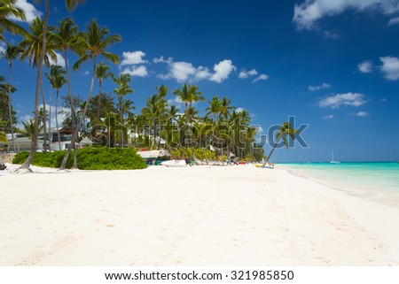 Luxury tourist resort on the tropical beach with palm trees in Dominican Republic - stock photo