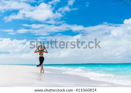 Luxury travel woman in black beachwear sarong walking taking a stroll on perfect white sand Caribbean beach. Girl tourist on summer holiday holding sun hat at vacation resort. Tropical landscape.