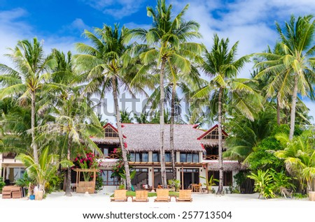 Luxury tropical villa near the sea with beautiful colorful decor, surrounding palm trees and lounges in front of it at famous exotic white sandy beach on Boracay island, Philippines. - stock photo