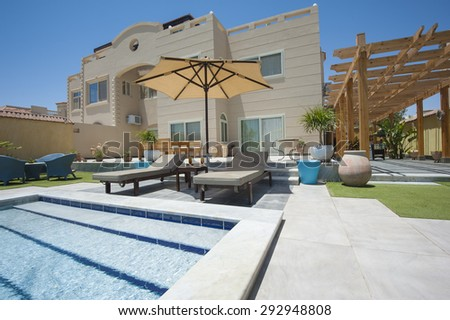 Luxury villa show home in a tropical resort with swimming pool and garden - stock photo