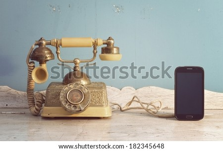 luxury vintage telephone and smartphone on white wooden classic table  - stock photo