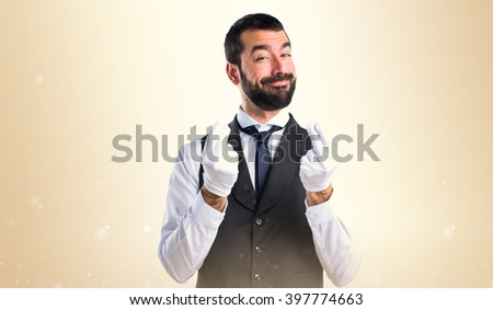 Luxury waiter doing a money gesture