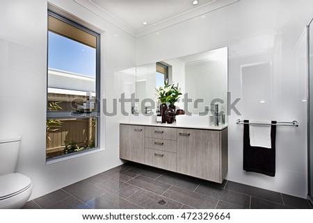 Luxury washroom with a window beside a bowl, giving the look of washroom interior, including a mirror with fancy vase and flowering plants, the towel is hanging on the wall, the outside can be seen