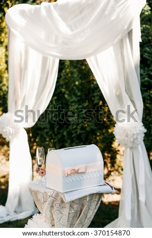 Luxury wedding arch of transparent white cloth beside the table with a box for wedding congratulations - stock photo