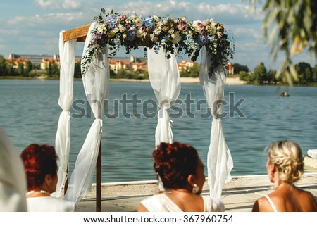 Luxury wedding arch with a transparent fabric, roses and plants on the sea, lake or river. - stock photo