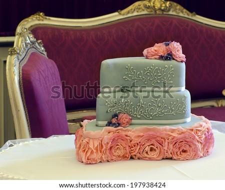Luxury wedding cake decorated with pink roses on table; antique furniture in background. - stock photo