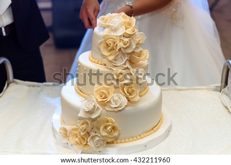luxury wedding cake decorated with roses at wedding reception, catering in restaurant - stock photo