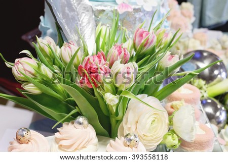 Luxury wedding decorations with beautiful bouquet of flowers and cakes. Floristic composition with pink and white tulips, green tulips leaves and buttercup - stock photo