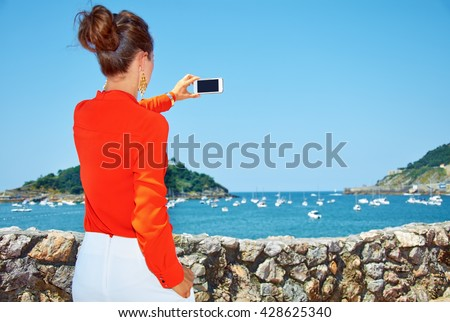 Luxury weekend retreat. Seen from behind woman in bright blouse taking photo with smartphone of the beautiful scenery overlooking lagoon with yachts - stock photo