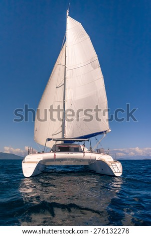 Luxury white catamaran floating in the ocean - stock photo