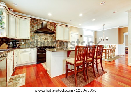 Luxury white kitchen with cherry hardwood and island with chairs. - stock photo