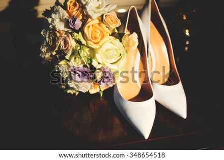 Luxury white leather women's high-heeled shoes on the table next to the magnificent colorful wedding bouquet of beautiful roses.