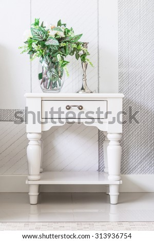 Luxury white vintage style Bedside table decor with beautiful flowers in a vintage room - stock photo