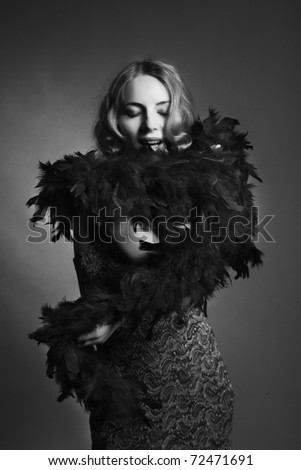 Luxury woman in a beautiful dress with boa (Dark Key photo) - stock photo