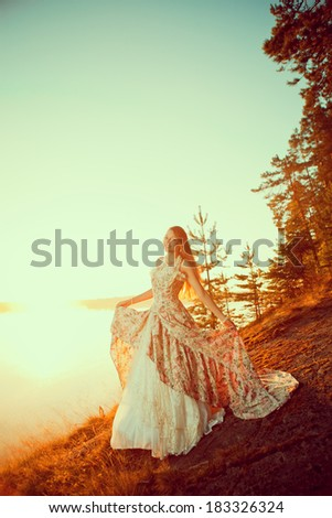 Luxury woman in a forest in a long vintage dress near the lake. Girl meets sunrise in summer forest - stock photo
