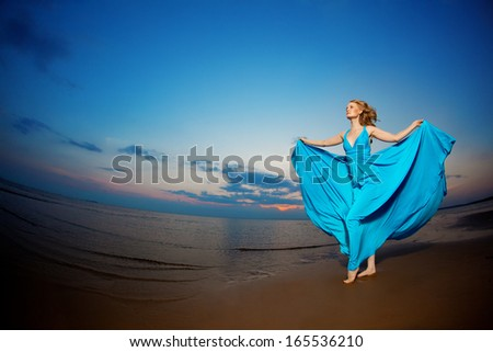 Luxury woman in a long blue evening  dress on the beach. Beautiful young girl at the  sea. - stock photo