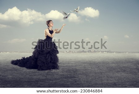 Luxury woman in a long dress of white doves released into the sky.