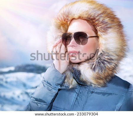 Luxury woman portrait in wintertime, wearing stylish sunglasses and warm coat with furry hood and looking away, winter fashion concept  - stock photo
