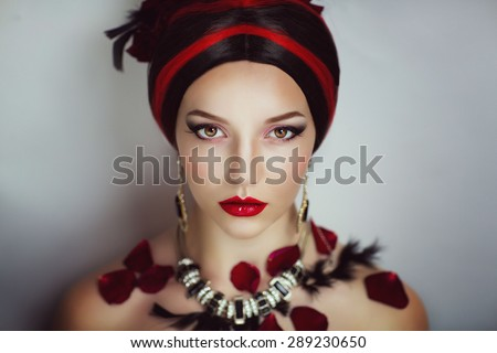 Luxury woman with black and red wig, expensive exclusive jewelry, earrings, necklaces, rose petals on the shoulders and black fluffy feathers. Professional horizontal Photo. Beautiful face young model - stock photo